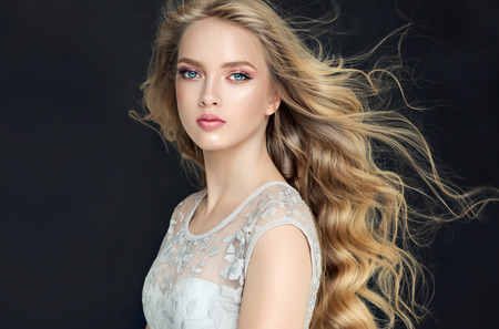 Young, blonde haired beautiful model with long, wavy,well groomed hair. Flying hair. Stock Photo