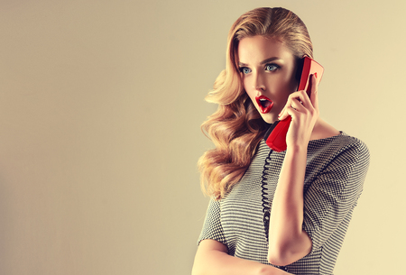 Expression of shock and excitement on the face of young woman  with old fashioned, red phone in her hand..Blonde in shock.