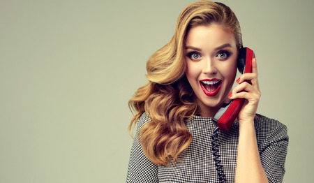 Blonde haired young woman with pin-up style makeup and hairstyle, is speaking by vintage phone. Extremely surprised and happy facial expression. Reklamní fotografie
