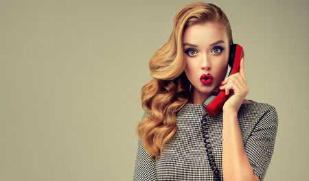 Expresión de asombro y asombro en el rostro de una mujer joven y hermosa de aspecto perfecto, con un teléfono antiguo y rojo en la mano. Expresión facial extremadamente sorprendida. Maquillaje estilo pin-up, peinado y manicura roja. Foto de archivo