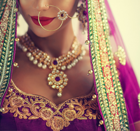 Young attractive woman, dressed in a traditional indian suit-sari, with purple blouse and shawl (dupatta) with gilded hand-made decoration. Posh jewelry set is consisting of big earrings, bright necklace and gold nose ring. Close-up details.