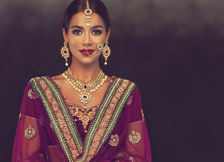 Portrait of beautiful girl dressed in a traditional indian national suit, jewelry set, blouse and shawl (dupatta). Banque d'images