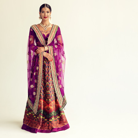 Young attractive woman, dressed in a traditional indian suit-sari. Splendid jewelry set, purple blouse and shawl (dupatta) with gilded hand-made decoration. Portrait in a full height. 免版税图像