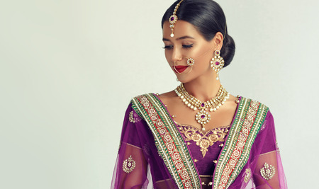 Young attractive woman, dressed in a traditional indian suit-sari, with purple blouse and shawl (dupatta) with gilded hand-made decoration. Posh jewelry set is consisting of big earrings, bright necklace, head adornment (tikka) and gold nose ring.