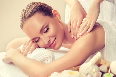 La mujer joven está recostada en la mesa de masaje y recibe tratamiento de masaje. Masaje de spa y cuerpo. Tensor y manos suaves del especialista en masaje están haciendo masajes en la espalda de una mujer joven y atractiva. Concepto de tratamiento de belleza y spa.