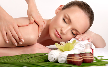 Young lady is laying on massage table and gets massage treatment.Spa and body massage.Tender and soft hands of massage specialist is making massage on the back of young and appealing woman. Beauty and Spa treatment concept.