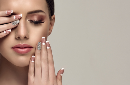 Young appealing woman is showing pale-pink french style manicure with  rhinestone on the slender fingers. Perfect makeup and trendy manicure.