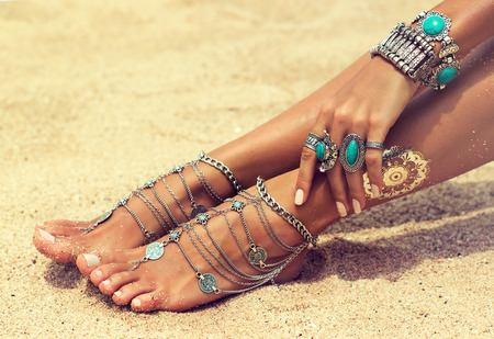 Womans hands and legs covered by bracelets and rings in a Boho style.Woman is sitting in relaxed position on tropical sandy beach. Body parts .