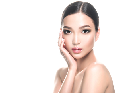 Gorgeous, young, asian black haired woman with clean fresh skin is touching the face. Oriental beauty. Facial treatment, cosmetology, beauty technologies and spa.