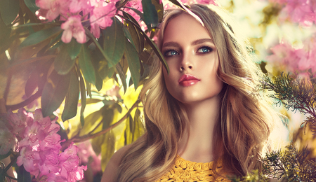 Magnificent young woman surrounded by blossoming flower trees. Gentle makeup, rose lipstick and freely lying long hair curls.