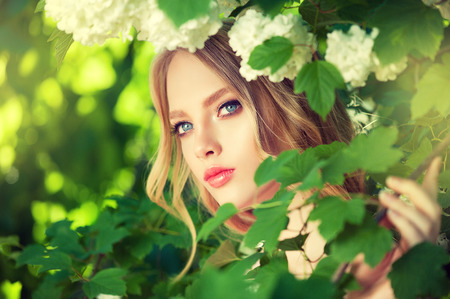 Beautiful young model in a spring blossoming garden. Symbol of blooming youth.