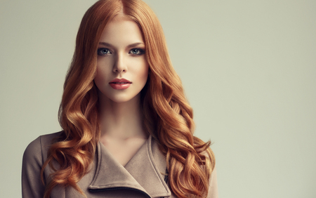 Young, red haired beautiful model with long, curly, well groomed hair. Excellent hair waves. 스톡 콘텐츠