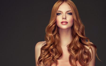 Giovane donna dai capelli rossi con i capelli ricci e voluminosi. Bellissima modella con taglio di capelli ondulato lungo e denso e trucco vivido. Onde di capelli perfetti e look appassionato.