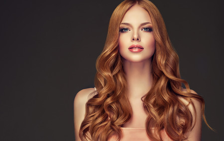 Young, red haired woman  with curly and voluminous hair. Beautiful model with long, dense wavy hairstyle and vivid make-up. Perfect hair waves and passionate look.
