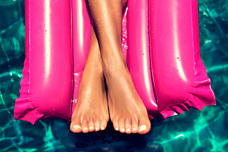 Tanned, well-groomed crossed womans feet is laying in the pool on magenta inflatable mattress for swimming. Pedicure, feet care and Spa. Simbolik image of comfortable rest in vacation.