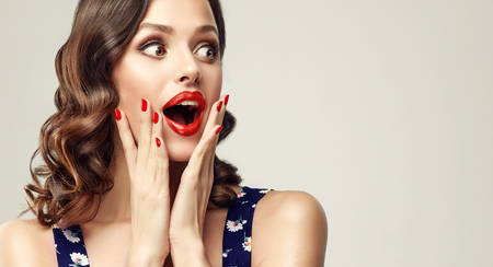 Expression of shock, excitement and amazement on face of perfectly looked, young, beautiful woman. Lady in shock. Pin-up style make up, and red manicure.