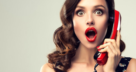 Expression of shock, excitement and amazement on face of perfectly looked, young, beautiful woman with old fashioned, red phone in her hand. Lady in shock. Pin-up style make up, and red manicure. Reklamní fotografie