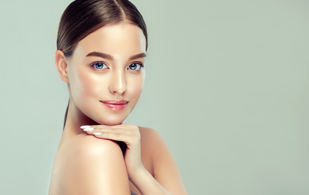 Gorgeous, young, brown haired woman with clean fresh skinis is touching gently the shoulder.  Light smile on the perfect face. Facial treatment, cosmetology, beauty technologies and spa. Stock Photo