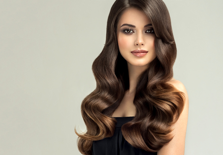 Jeune femme aux cheveux bruns avec des cheveux bouclés et volumineux. Beau modèle avec une coiffure ondulée longue et dense et un maquillage vif. Vagues de cheveux parfaites et look sexy.Cheveux incroyablement onduleux et brillants. Banque d'images
