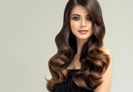 Junge, braunhaarige Frau mit lockigem und voluminösem Haar. Schönes Modell mit langer, dicht gewellter Frisur und lebhaftem Make-up. Perfekte Haarwellen und sexy Look. Unglaublich welliges und glänzendes Haar. Standard-Bild