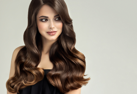 Young, brown haired woman  with curly and voluminous hair. Beautiful model with long, dense wavy hairstyle and vivid make-up. Perfect hair waves ,tender and calm look.Incredibly undulating and shiny hair. Stock Photo