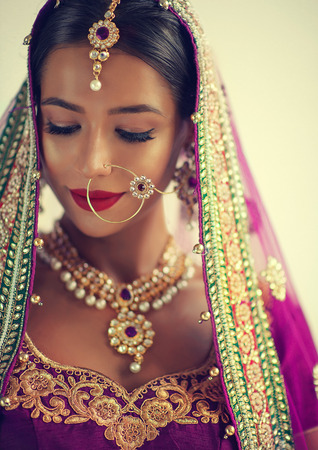 Young attractive woman, dressed in a traditional indian suit-sari, with purple blouse and shawl (dupatta) with gilded hand-made decoration. Posh jewelry set is combining of big earrings, bright necklace and gold nose ring. All items made in Kundan jewelry style. Close-up portrait. Banque d'images - 99517415