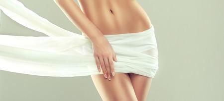 Parte del atractivo cuerpo de la mujer, las caderas y el esbelto vientre tonificado, cubierto por un tierno tejido de seda. Graciosa figura femenina, como símbolo de salud y armonía. Bien posando modelo está demostrando un gesto elegante y una figura sana y elegante. Foto de archivo