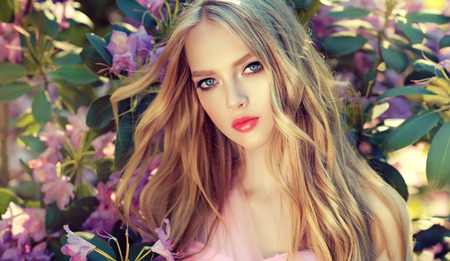 Gorgeous young woman surrounded by blossoming flower trees. Gentle makeup, rose lipstick and freely lying long hair curls. Spring style. Spring blossom and bloom of youth.