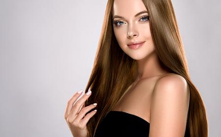 Young, brown haired woman  with voluminous hair.Beautiful model with long, dense, straight hairstyle and vivid makeup, is touching own hair with tenderness. Imagens - 102746304