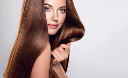 Joven, mujer de cabello castaño con cabello voluminoso.Hermosa modelo con peinado largo, denso y recto y maquillaje vivo, toca su propio cabello con ternura.