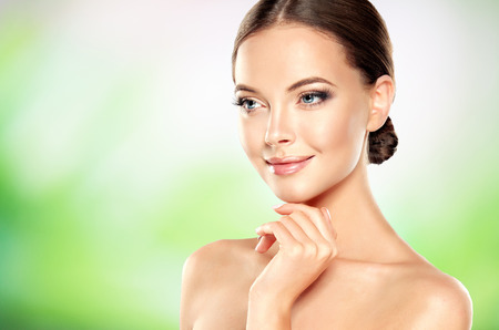 Girl with clean fresh skin is touching the face and tenderly smiling to viewer. Physical perfection and emotion balance. Facial treatment, cosmetology, beauty technologies and spa. Stock Photo