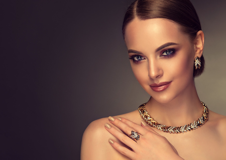 Pretty model with smoky-eyes makeup style is demonstrating gilded jewelry set. Gilded jewelry set containing earrings, necklace and ring is dressed on young perfectly looking woman.