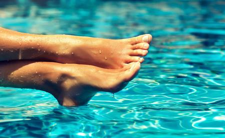 Opalone, zadbane, skrzyżowane stopy kobiety, pokryte kroplami czystej wody, spoczywają nad niebieską, ruchomą powierzchnią basenu. Pedicure, pielęgnacja stóp i Spa.