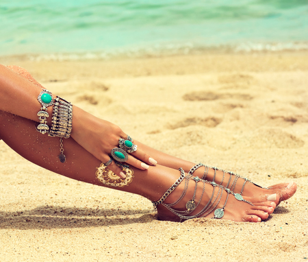 Womans hands and legs covered by silver bracelets and rings in a Boho style.Woman is sitting in relaxed position on the sand of tropical beach. Pedicure, feet care and Spa. Body parts.