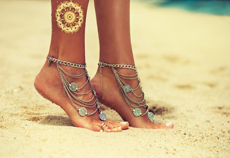 Tiptoed woman's feet covered by boho style jewelry is standing on the tropical sand. Tanned, well-groomed woman's feet with white color pedicure decorated by stylish boho objects.