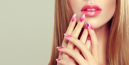 White, perfect teeth behind beautiful lips with ideal shape and colored by rose lipstick. Multi coloured, rose and white manicure on the nails. Fashion makeup and cosmetic.