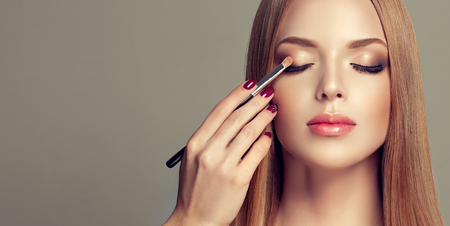 Professional makeup artist is coloring eyelids of perfectly looking young model. Double-colored, gilded eyelids and rose lipstick. Makeup in progress. Fashion, makeup and cosmetic.