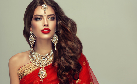 Young attractive woman, covered by traditional indian red shawl (dupatta) and dressed in hand-made kundan style jewelry set. Posh jewelry set is consisting of big earrings, bright necklace and head adornment (tikka). Perfect, dense, wavy, freely flying hair and smoky eyes style makeup. 版權商用圖片