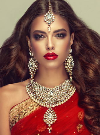"Young attractive woman, covered by traditional indian red shawl (dupatta) and dressed in hand-made ""kundan style"" jewelry set. Posh jewelry set is consisting of big earrings, bright necklace and head adornment (tikka). Perfect, dense, wavy, freely flying hair and ""smoky eyes"" style makeup."