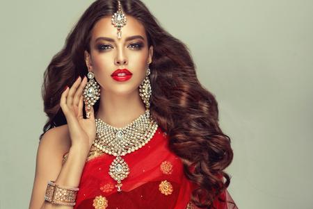 """Mujer joven y atractiva, cubierta con un tradicional chal rojo indio (dupatta) y vestida con un conjunto de joyas """"estilo kundan"""" hechas a mano. El juego de bisutería elegante consta de aretes grandes, collar brillante y adorno para la cabeza (tikka). Cabello perfecto, denso, ondulado, que vuela libremente y maquillaje estilo """"ojos ahumados""""."""