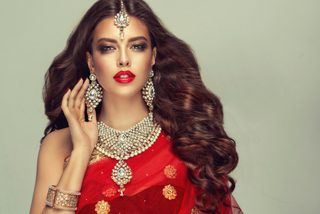 Young attractive woman, covered by traditional indian red shawl (dupatta) and dressed in hand-made kundan style jewelry set. Posh jewelry set is consisting of big earrings, bright necklace and head adornment (tikka). Perfect, dense, wavy, freely flying hair and smoky eyes style makeup. Imagens