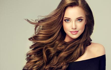 Junge, braunhaarige Frau mit voluminösem Haar. Wunderschönes Modell mit langer, dichter, lockiger Frisur und lebendigem Make-up. Perfektes dichtes, welliges und glänzendes Haar. Friseurkunst, Haarpflege und Schönheitsprodukte. Standard-Bild