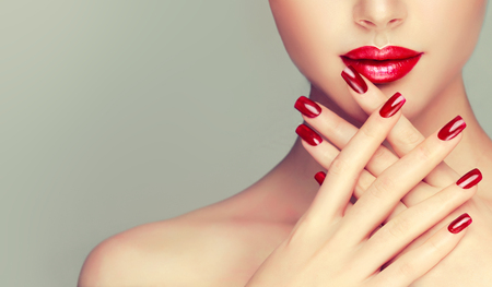 Perfect woman lips with ideal shape and colored by bright red lipstick and red manicure on the nails.Stylish evening image for young women. Fashion makeup and cosmetic.