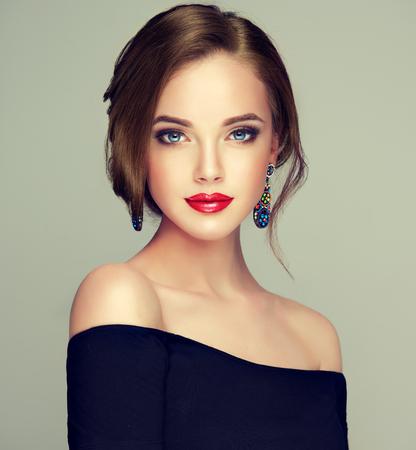 Retrato de joven hermosa mujer de cabello castaño con cabello largo y bien cuidado recogido en elegante peinado de noche. Arte de peluquería, cuidado del cabello y productos de belleza. Foto de archivo
