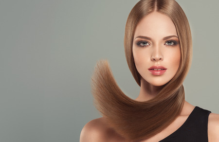 Young, brown haired woman  with straight and voluminous hair. Beautiful model with long, dense straight hairstyle and vivid make-up. Perfect flying hair and sexy look. Stock Photo