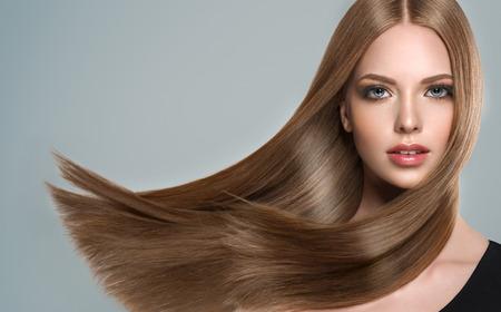 Junge, braunhaarige Frau mit glattem und voluminösem Haar. Schönes Modell mit langer, dichter, gerader Frisur und lebendigem Make-up. Perfektes fliegendes Haar und Aussehen.