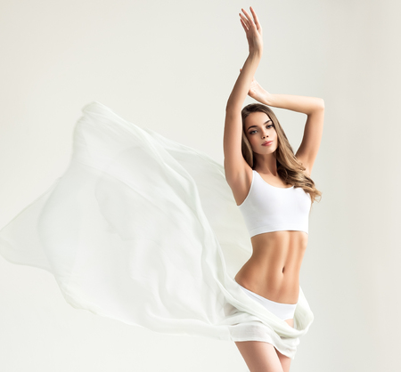 Young alluring woman with graceful and slim body dressed in a white sport underwear and partially covered by tender, silk textile. Slender female figure, as a symbol of health and harmony. 版權商用圖片 - 107003550