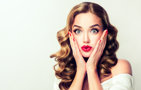 Expression of shock, excitement and amazement on face of perfectly looked, young, beautiful woman. Blonde in shock. Telling facial expression. Pin-up style make up, and red manicure.