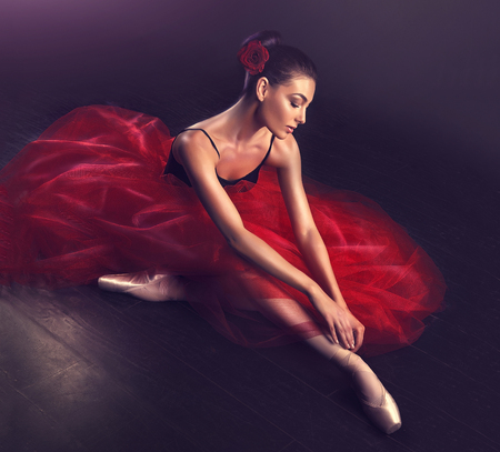 Beauty of classic ballet. Ballerina is performing classic dance. Young graceful ballet dancer dressed in a classic  theatrical outfit  is sitting on the floor of stage in a pose of dying swan.