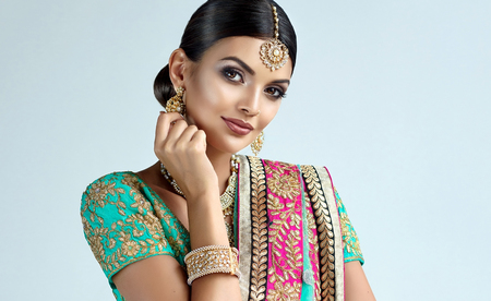 Young attractive woman, dressed in a traditional indian suit-sari, with green blouse and shawl (dupatta) with gilded hand-made decoration. Foto de archivo